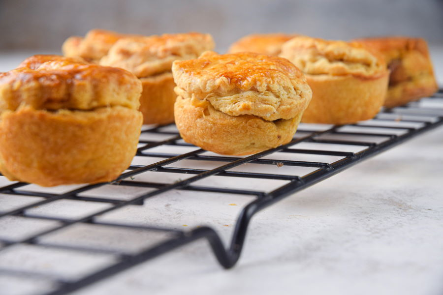 Mini apple pies on baking grid and light background.