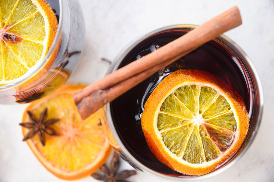 Electric Skillet Mulled Wine in wine glasses with orange slices and cinnamon sticks.