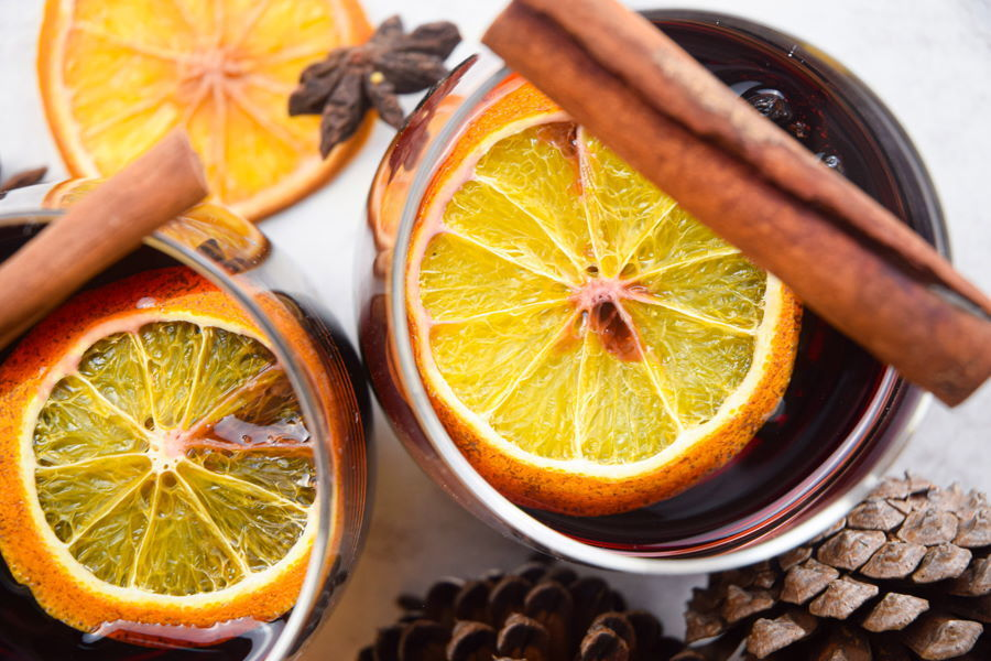 Electric Skillet Mulled Wine in wine glasses with orange slices and cinnamon sticks, acorns in the background.