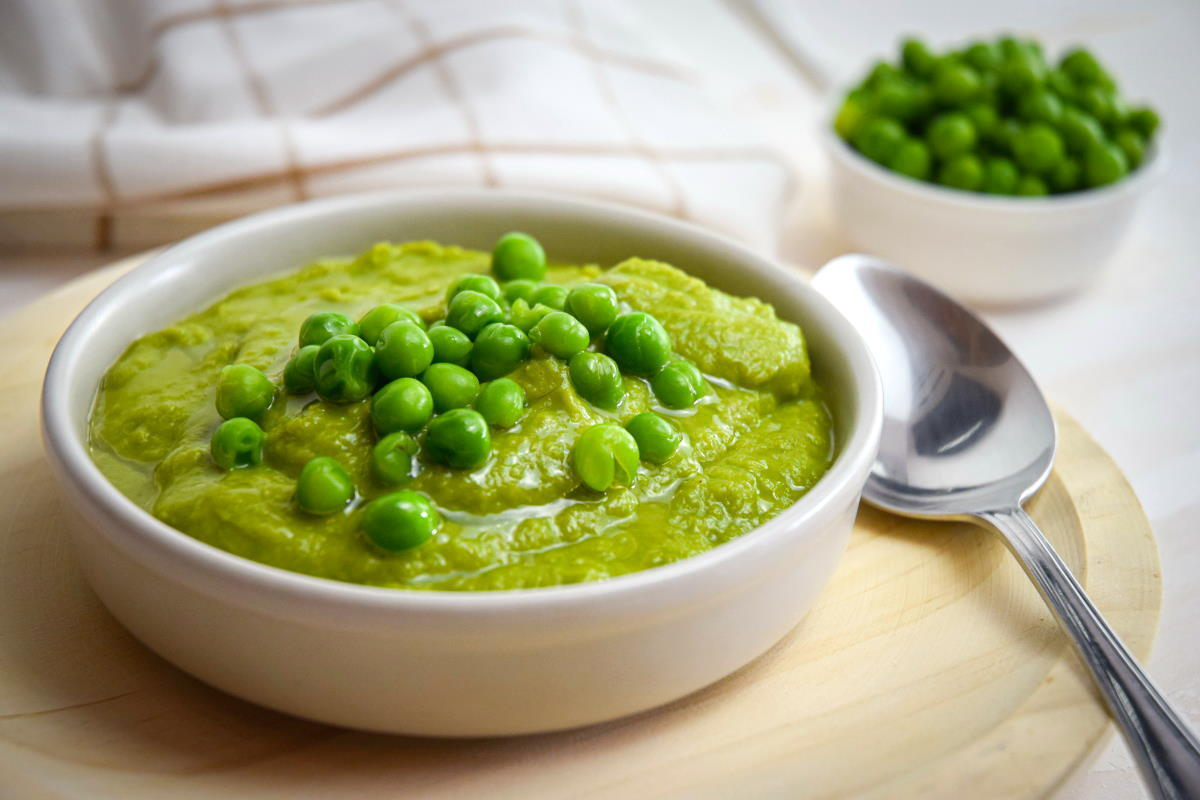 Pea purée in a white bowl on wooden plate, with a spoon on the side