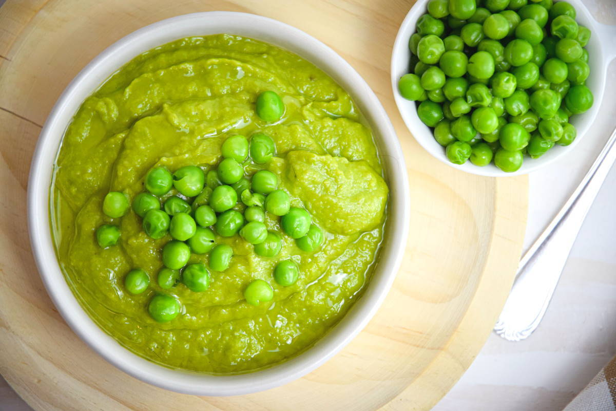 Pea purée in a white bowl on wooden plate, with green peas in the background.