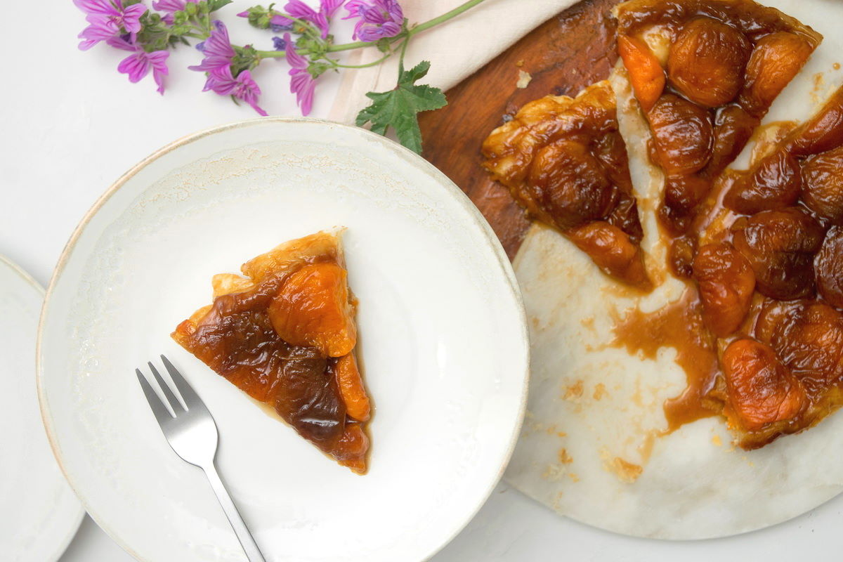 Peach Tarte Tatin slice on a white plate, purple flowers in the background.