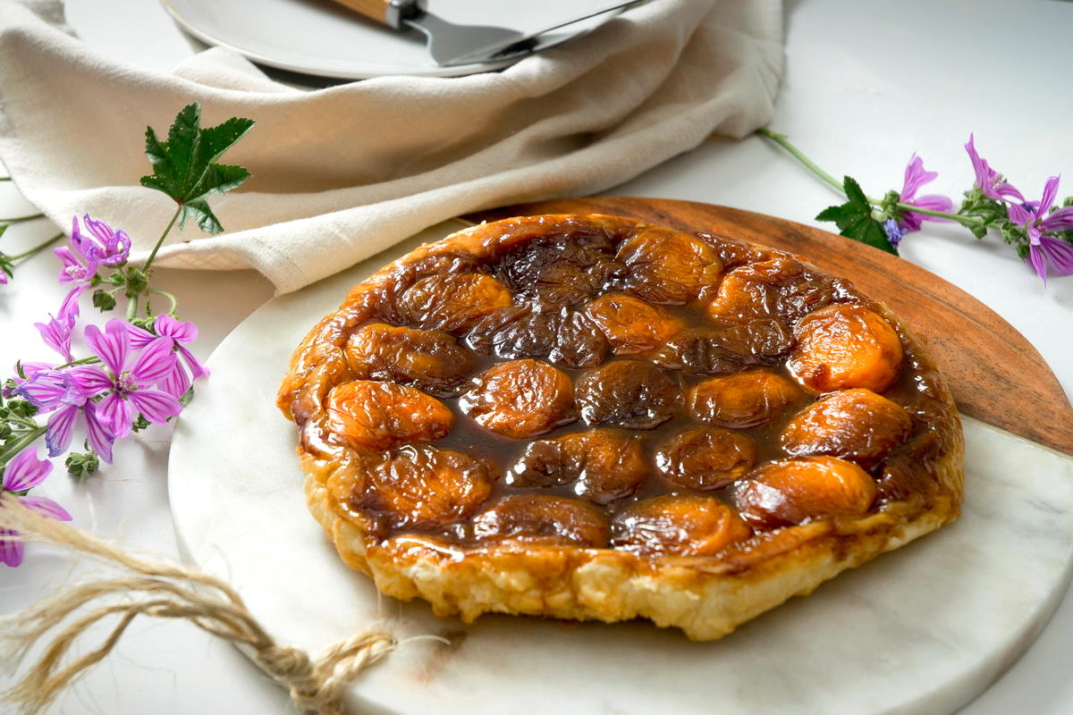 Peach Tarte Tatin on a marble and wooden serving board, purple flowers in the background.
