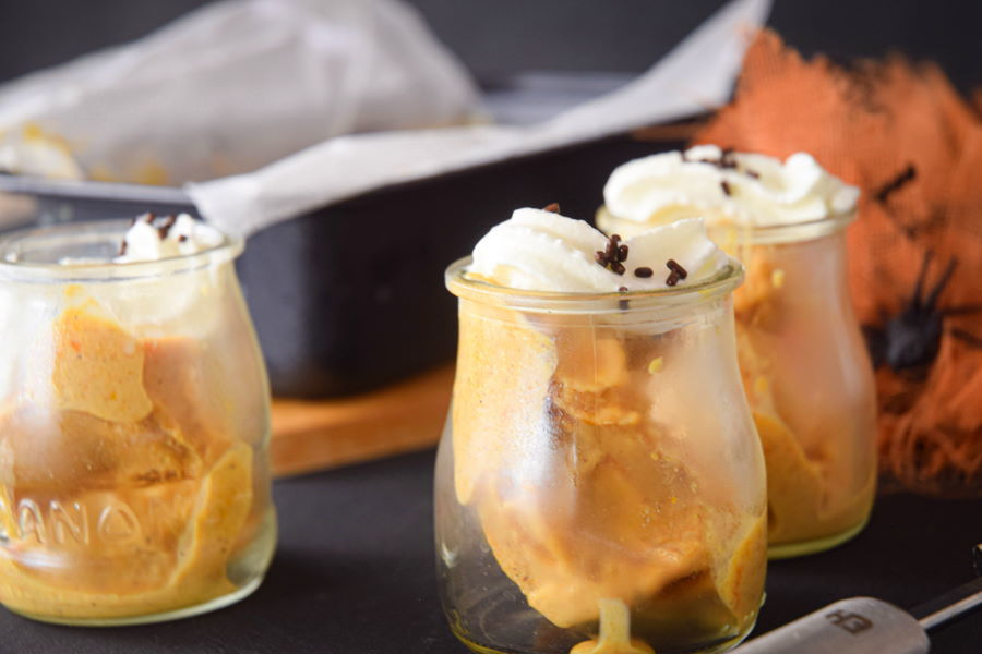 Pumpkin spice ice cream in small glass jars with orange fabric and plastic spiders.