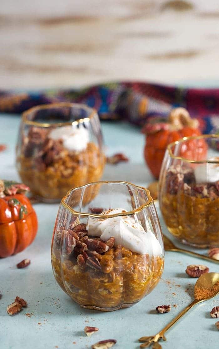 Pumpkin overnight oats in clear glass dessert dishes.