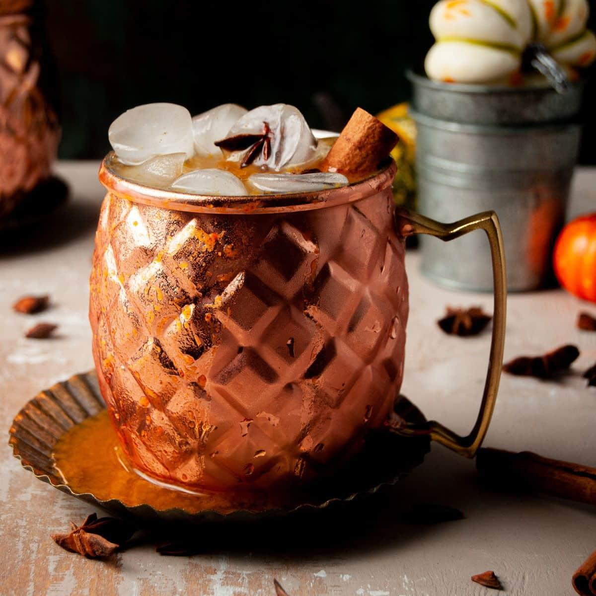 Pumpkin spice mule in copper mug with ice and a cinnamon stick.