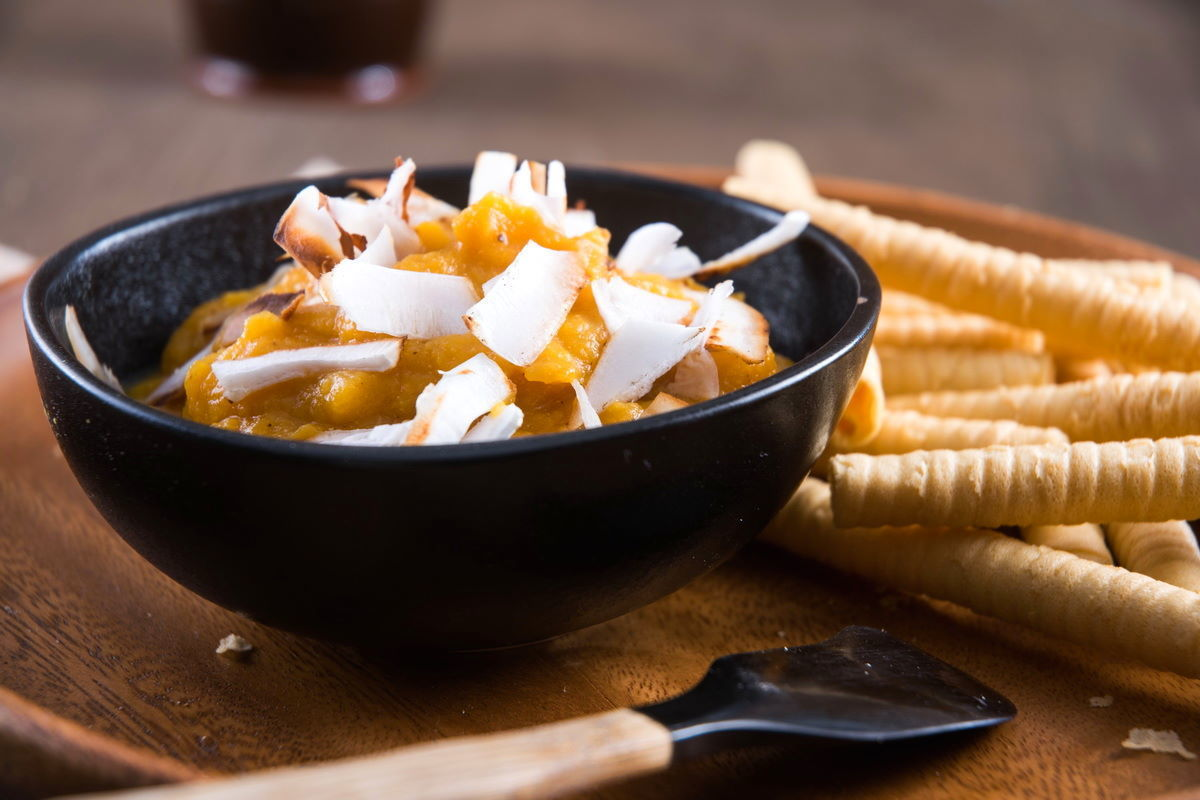 Pumpkin pie hummus in a bowl with toasted coconut flake topping, breadsticks on the side.