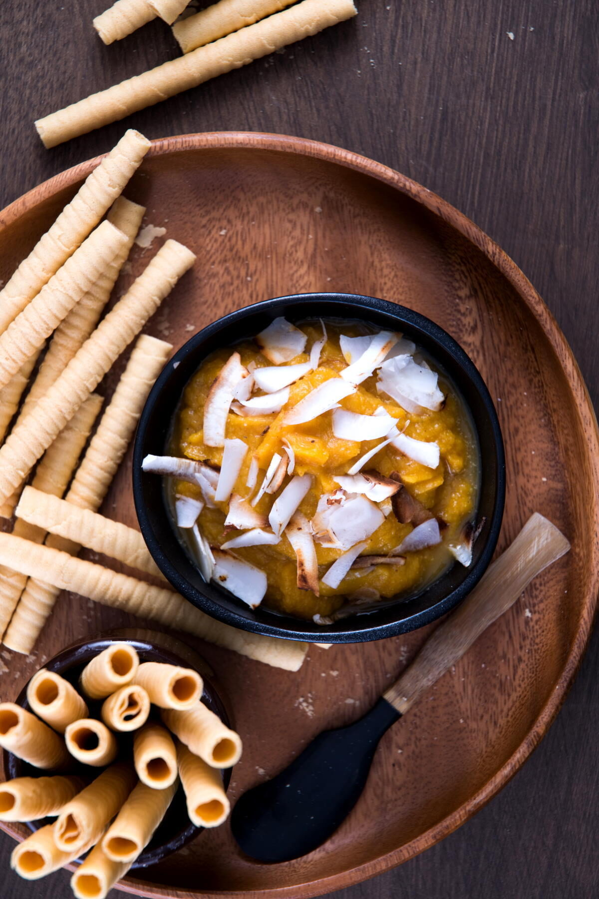 Pumpkin pie hummus in a black bowl on wooden plate with toasted coconut flake topping, breadsticks and small spatula on the side.