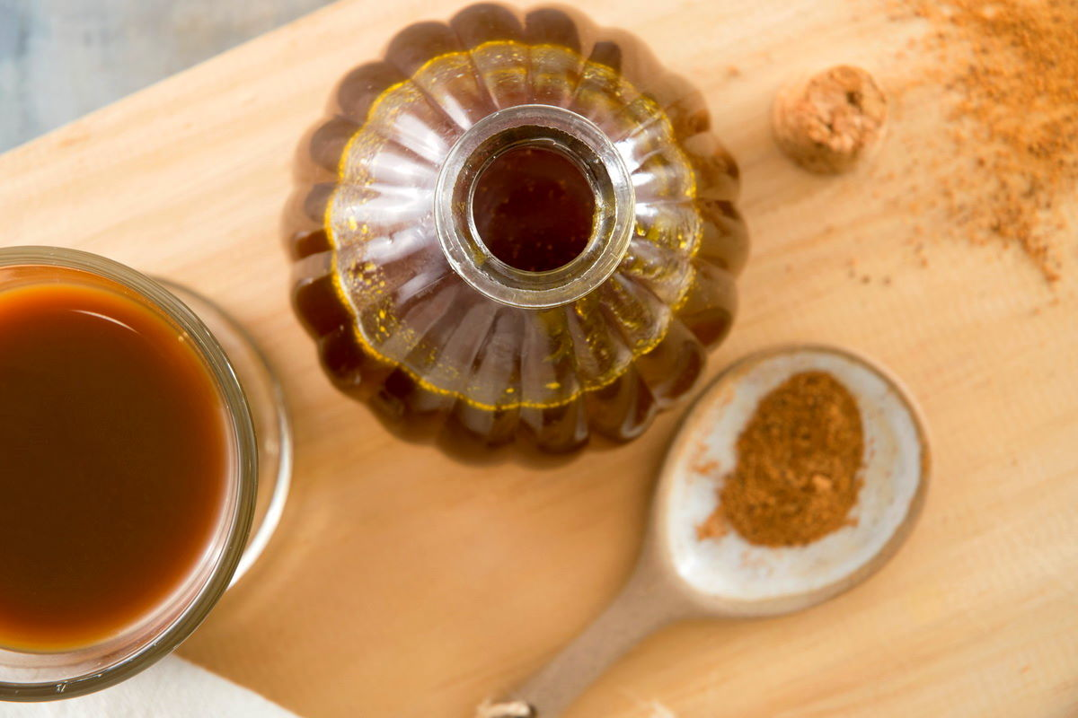Pumpkin spice syrup in a small decorative jar, a spoon of pumpkin pie spice and a glass of pumpkin spice latte on the side.