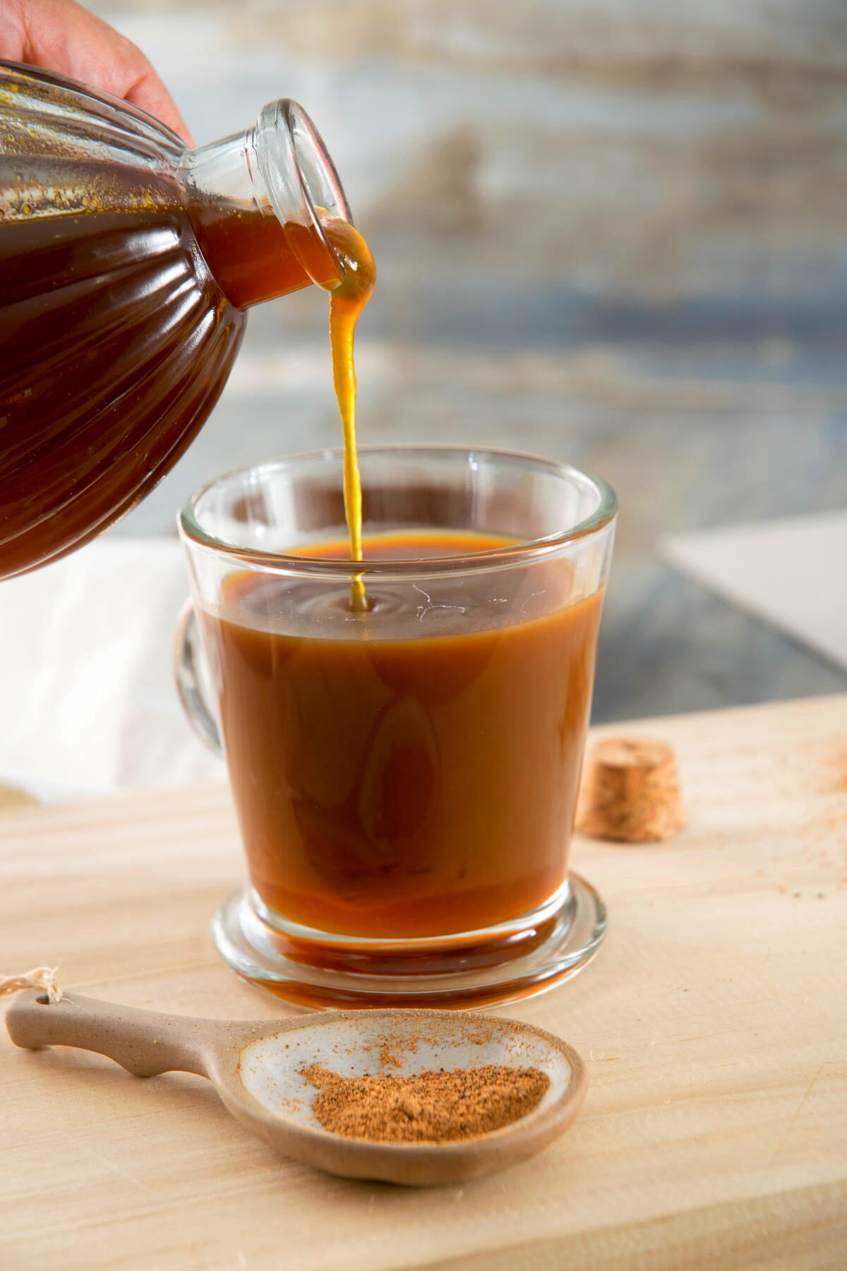 Pumpkin spice syrup pouring into a clear, glass mug of coffee.