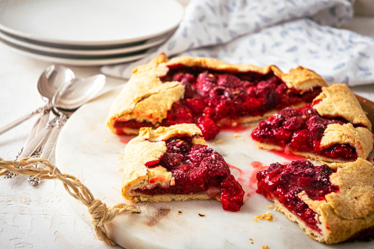 Raspberry Galette on a serving board, spoons and plates on the side.
