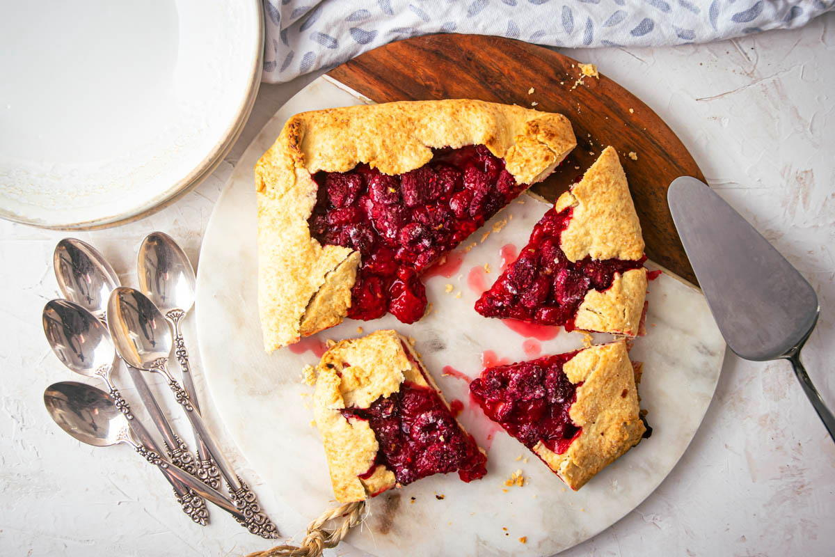 Raspberry Galette sliced on a serving board, spoons and plates on the side.