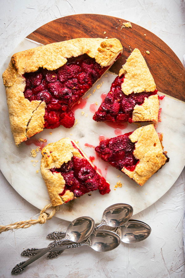 Raspberry Galette sliced on a serving board, spoons on the side.