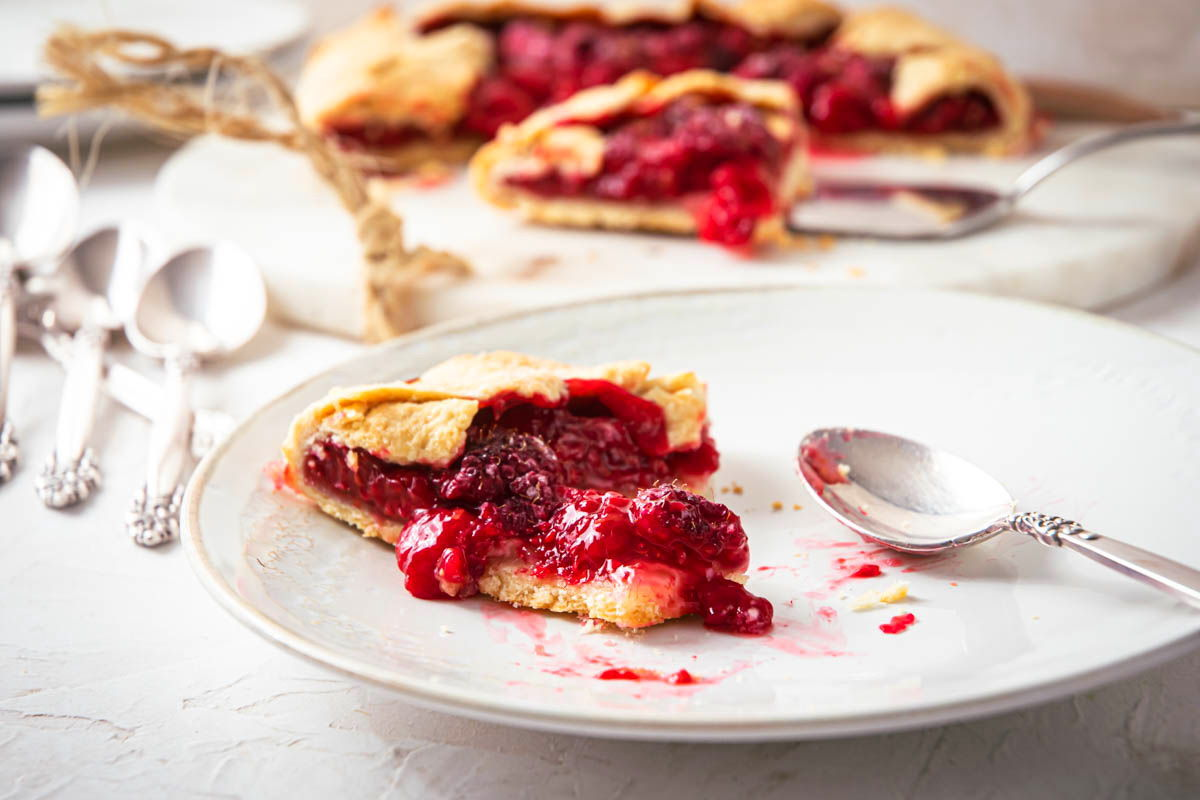 A piece of raspberry galette on a white plate, spoons on the side.