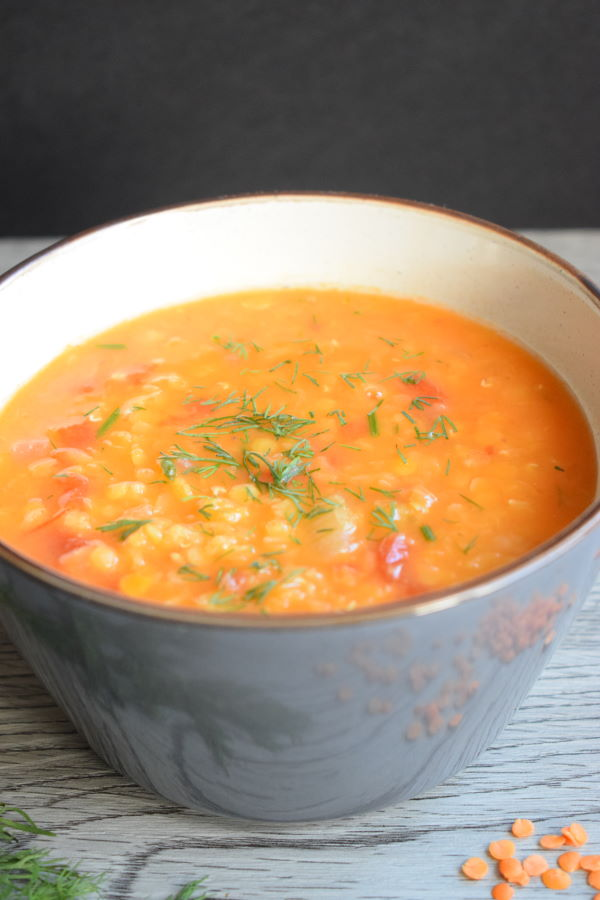 Red lentil dill soup in a blue bowl, wooden background.