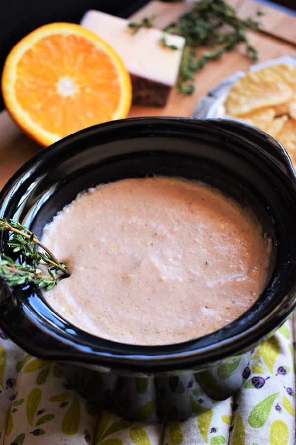 Red wine and cheese dip in a mini crockpot with an orange and cheese block on the side, wooden background.