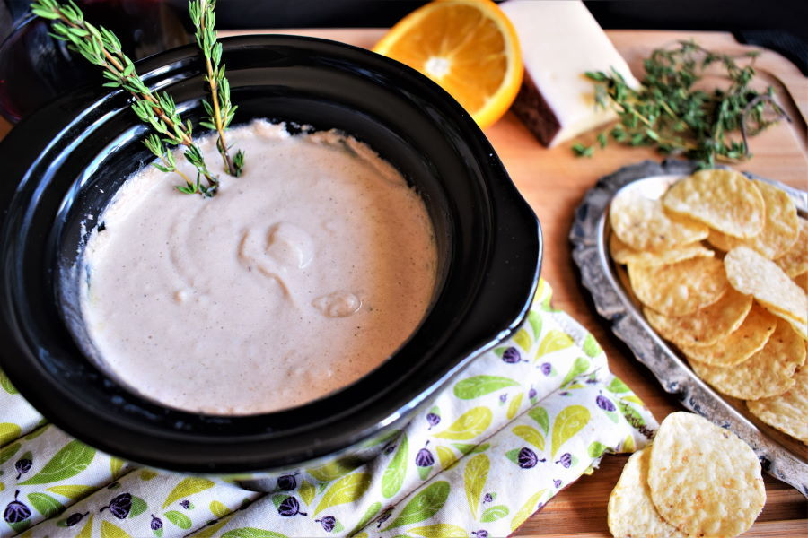 Red wine and cheese dip in a mini crockpot with tortilla chips on the side, wooden background.