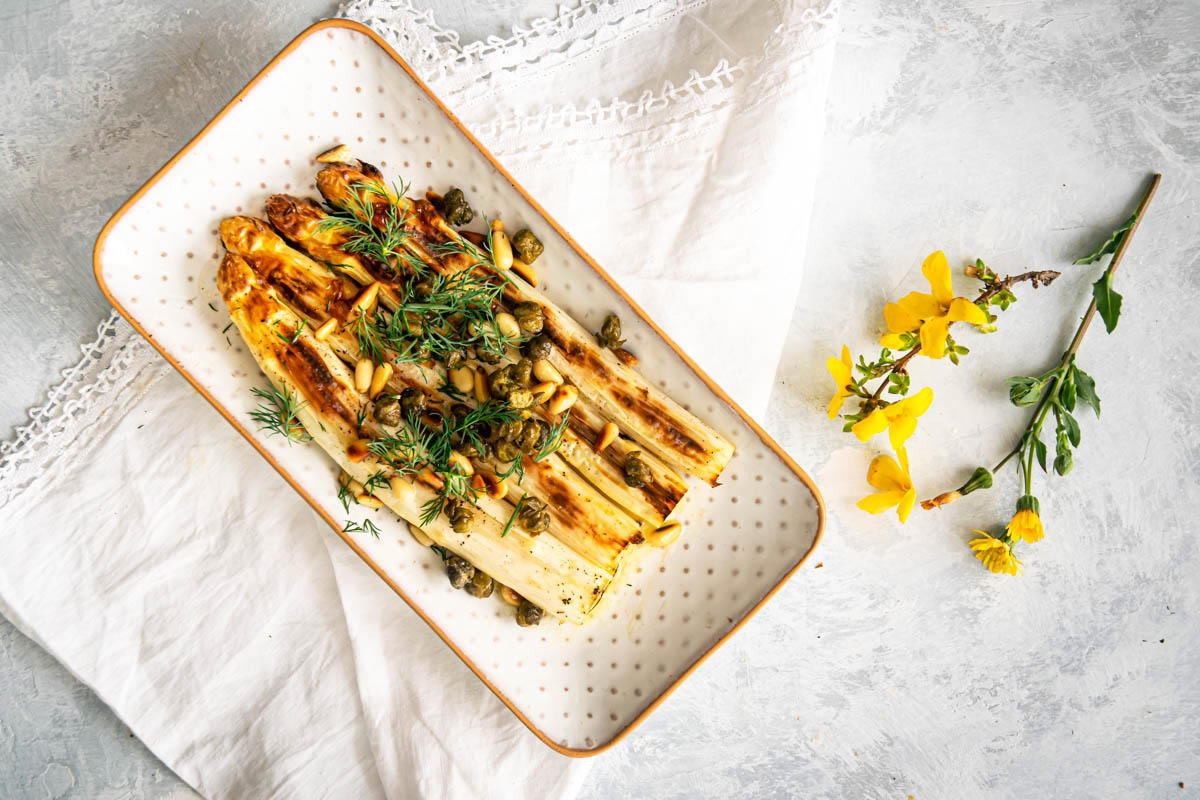 Roasted White Asparagus in a porcelain serving dish, a white table cloth and yellow flowers on the side.