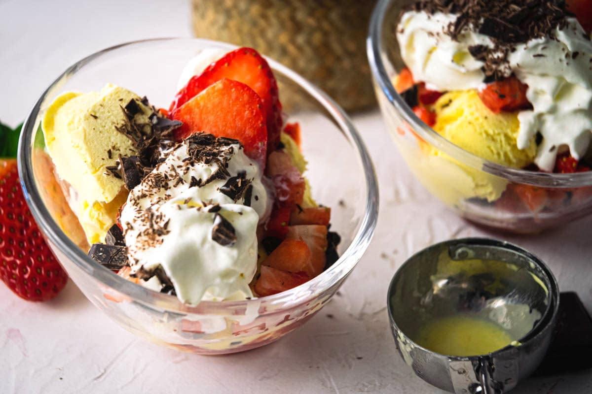 2 strawberry sundaes in dessert bowls, strawberries on the side.