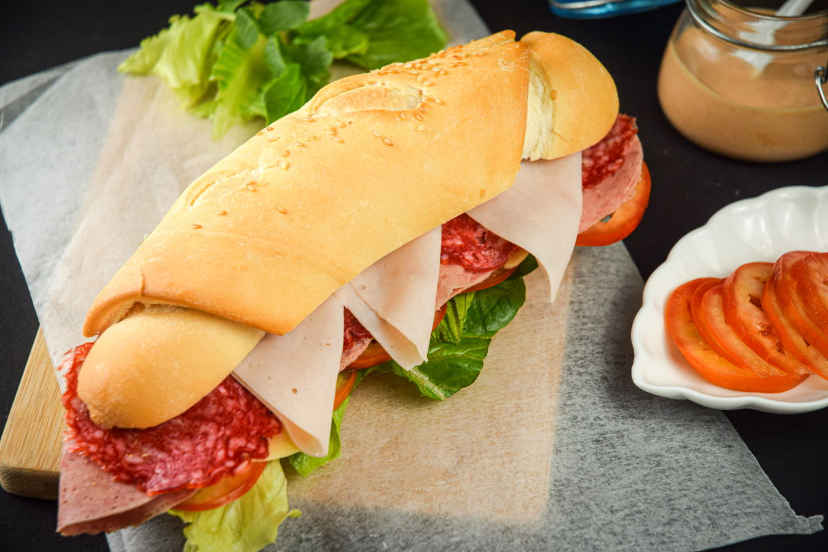 Triple meat sub sandwich with sriracha sauce on wooden cutting board and deli paper.