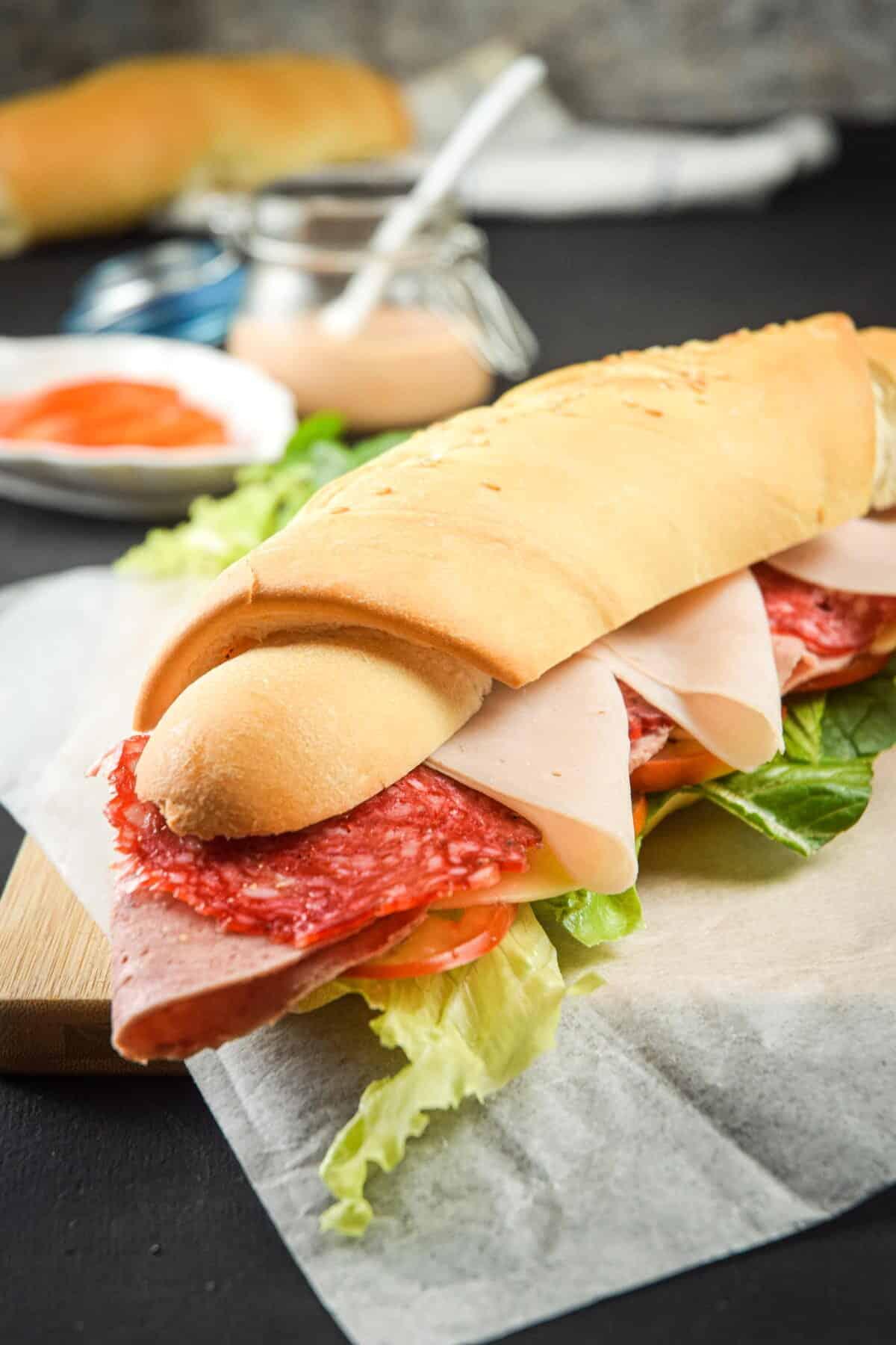 Triple meat sub sandwich with sriracha sauce on wooden cutting board.