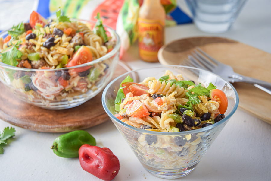 Taco pasta salad in clear bowls. Light background, bell peppers and forks on the side.