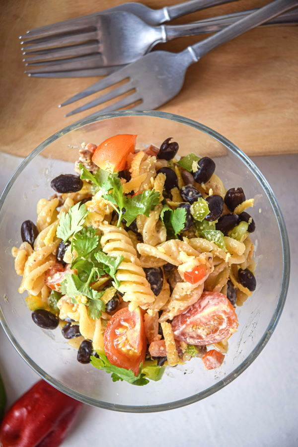 Taco pasta salad in a clear bowl with a red peppers and forks on the side.