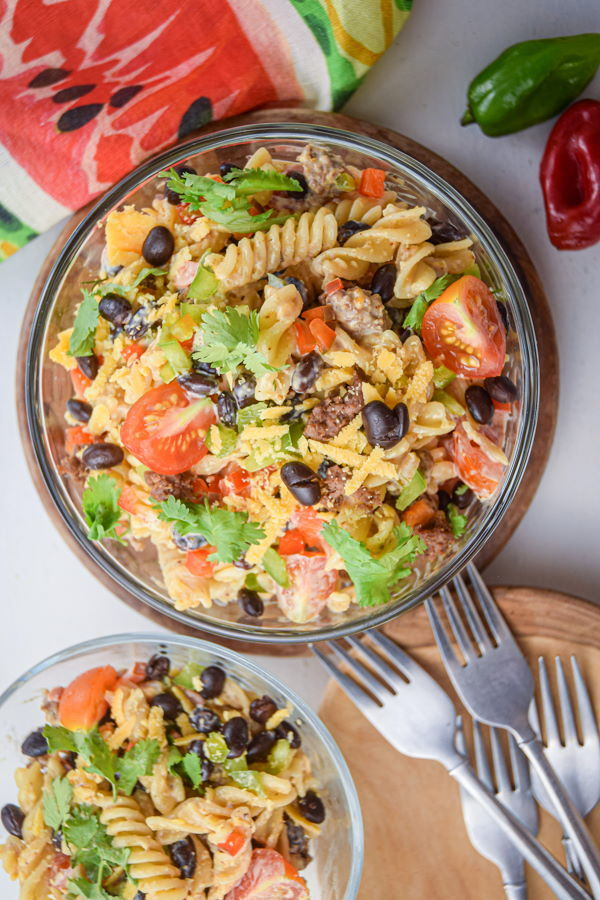 Taco pasta salad in clear bowls with forks and peppers on the side.