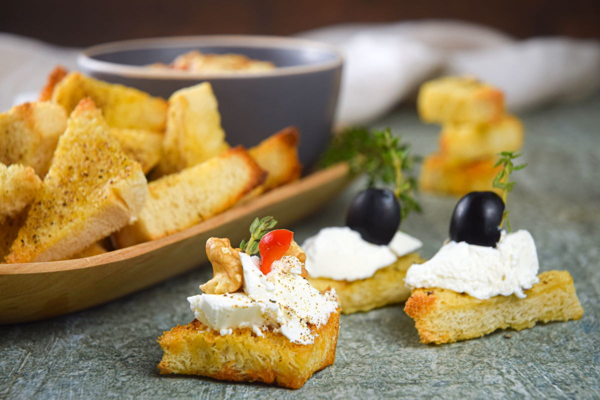 Toast points with cream cheese and black olive toppings.