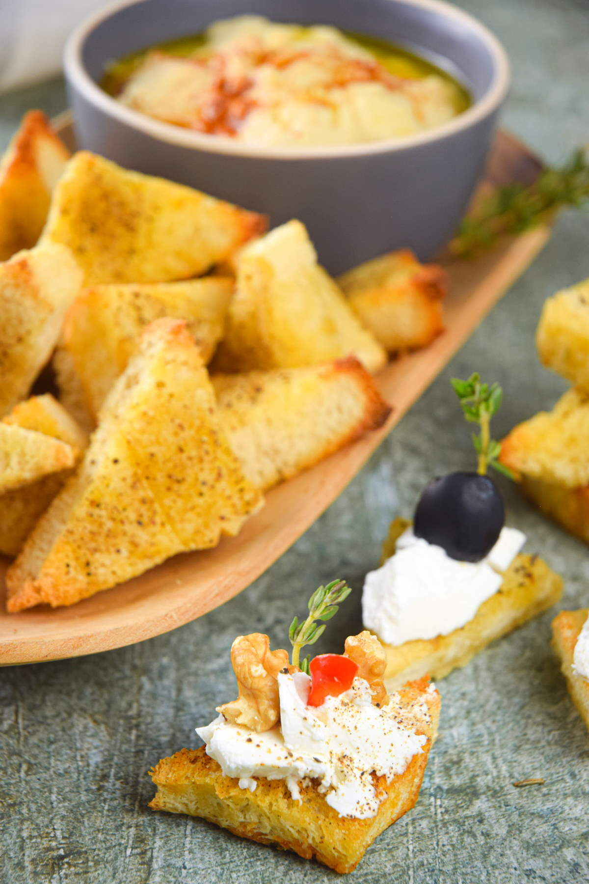 Toast points on serving board with bowl of hummus and cream cheese topping.