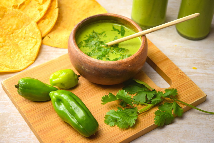 Tomatillo hot sauce in bottles and a bowl. Tortillas, peppers and cilantro on a cutting board.