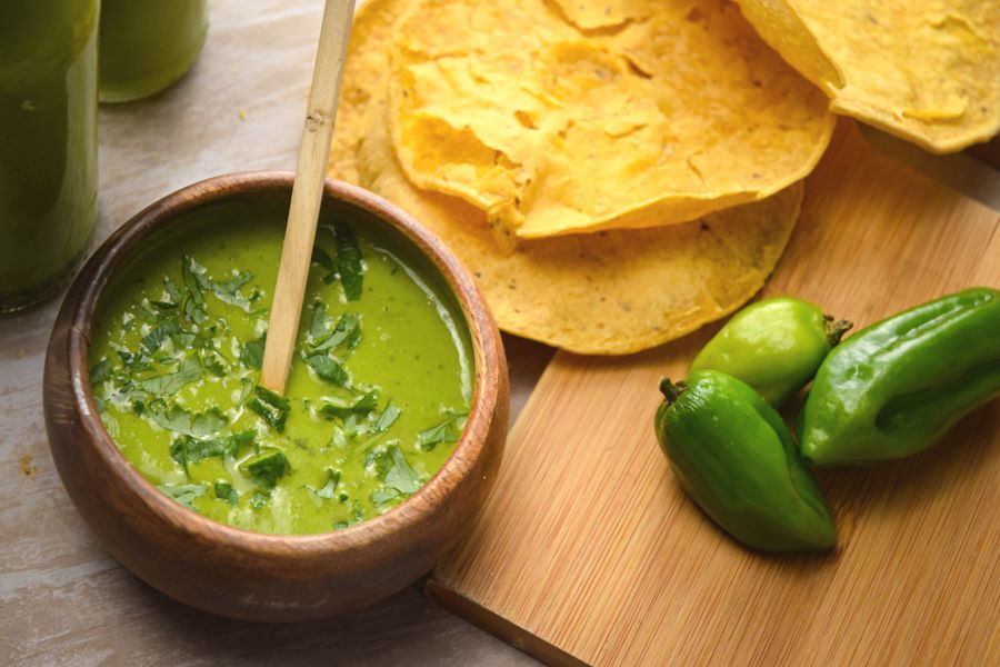 Tomatillo hot sauce in a wooden bowl, tortillas and peppers on the side.