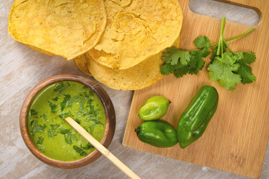 Tomatillo hot sauce in a wooden bowl, tortillas, cilantro and peppers on the side.
