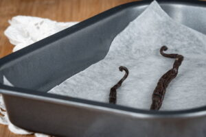 Vanilla beans pods sitting in a baking tray.