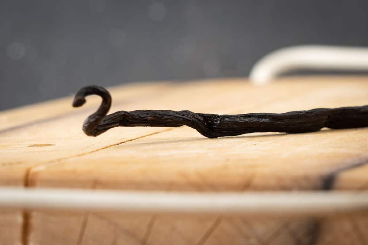 Vanilla bean pod on a cutting board.
