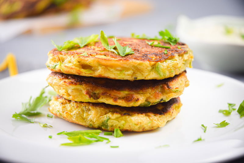 Vegetarian Zucchini Crab Cakes on a white plate with chopped parsley.