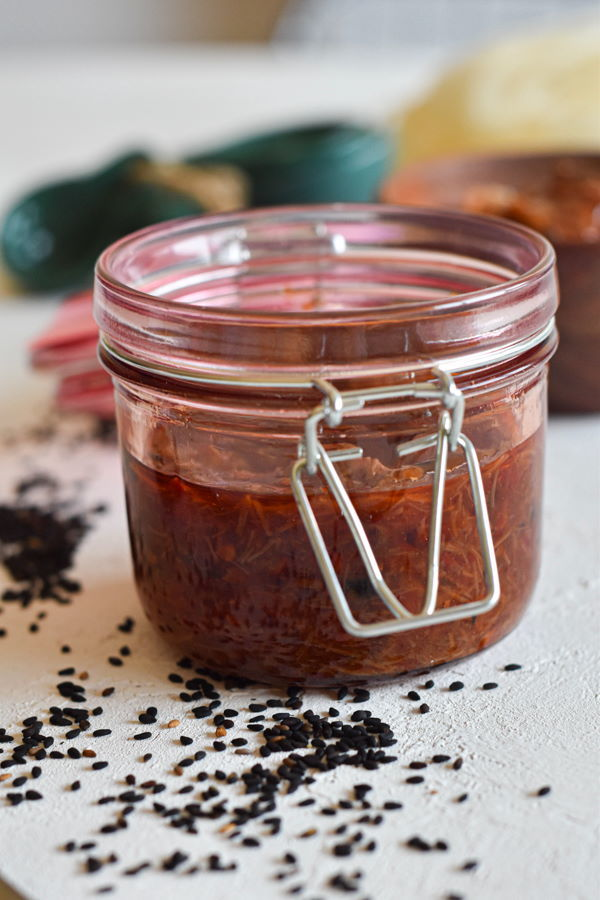 XO sauce in a jar on white background with black sesame seeds scattered around.