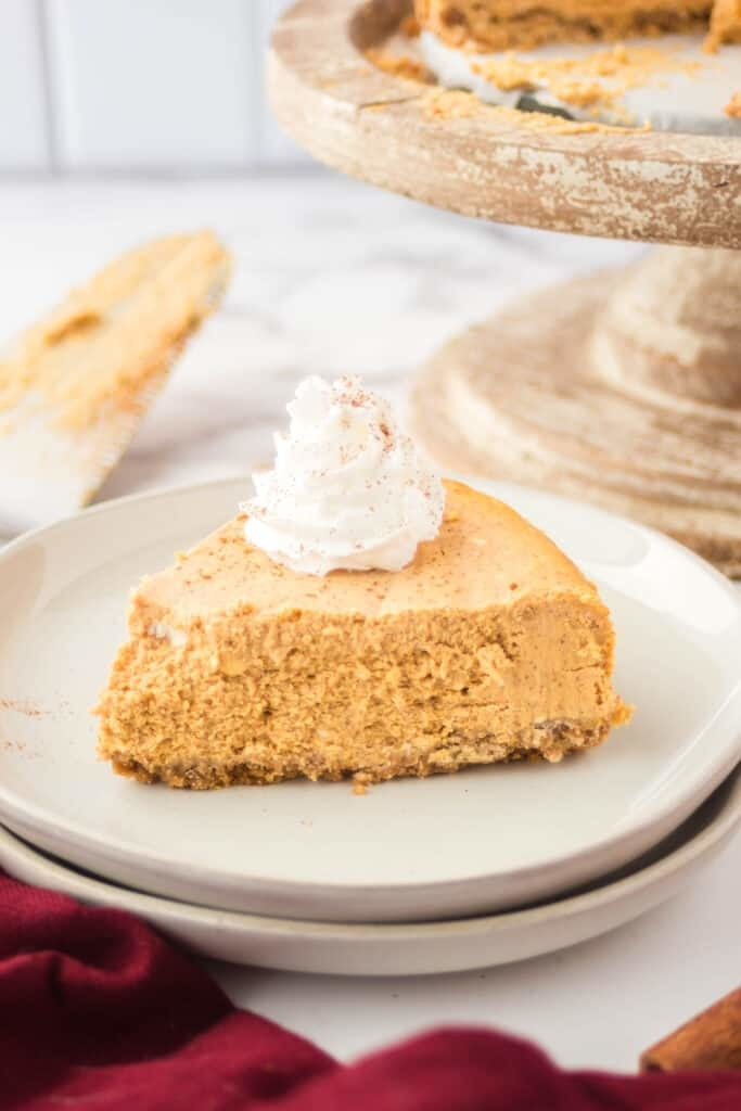 A slice of pumpkin cheesecake on white plate.