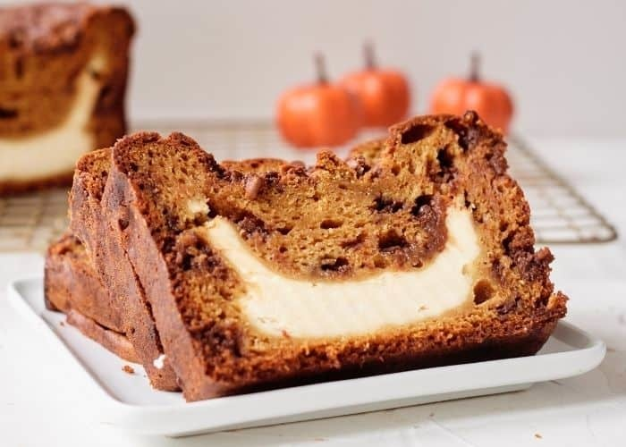 Pumpkin loaf with cream cheese filling on baking rack.