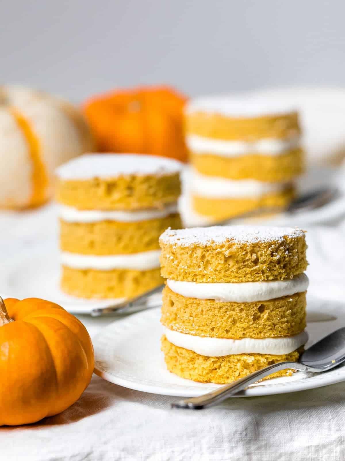 Mini pumpkin layer cakes on white plates.