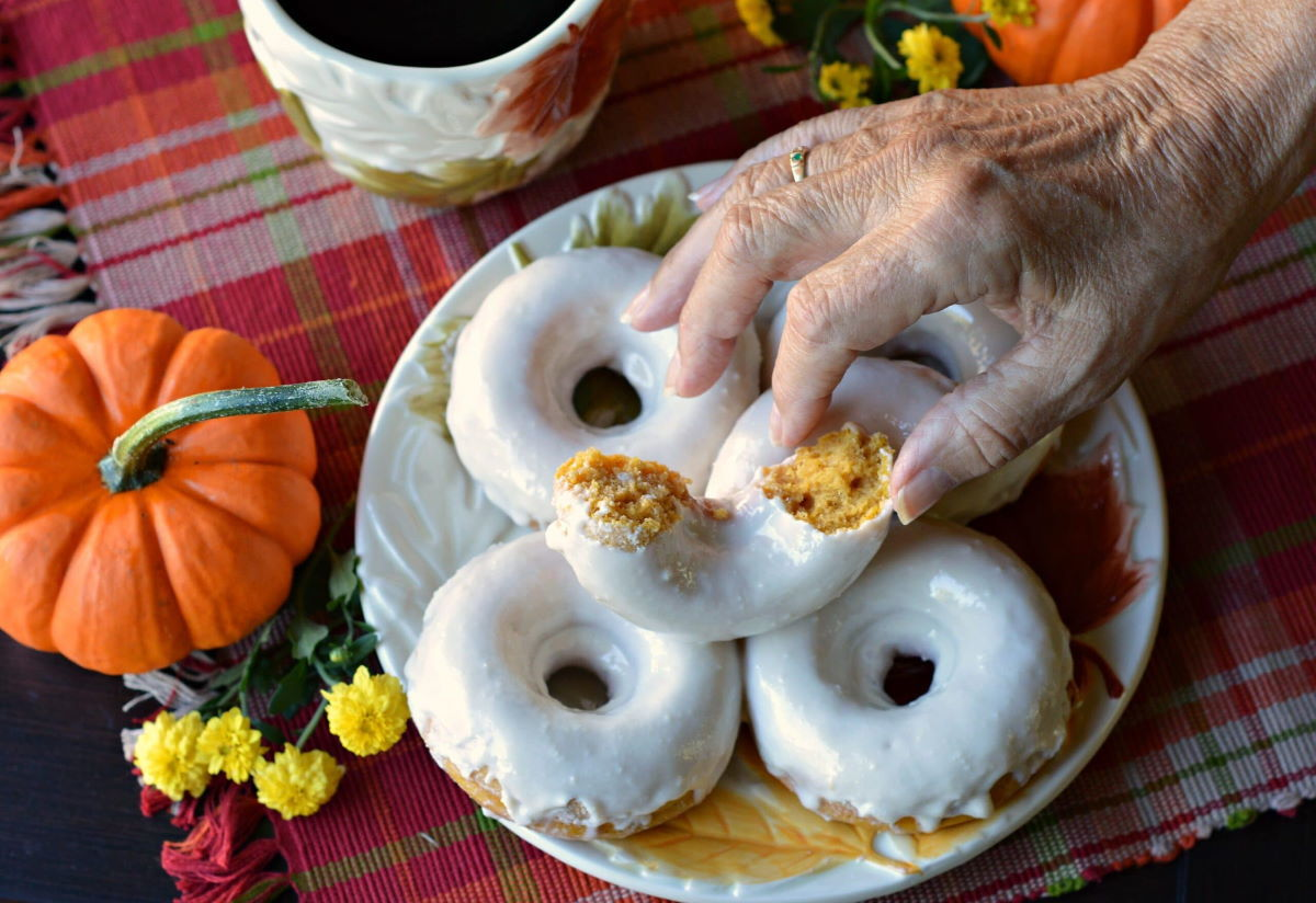 Pumpkin donuts with gourds on the side.