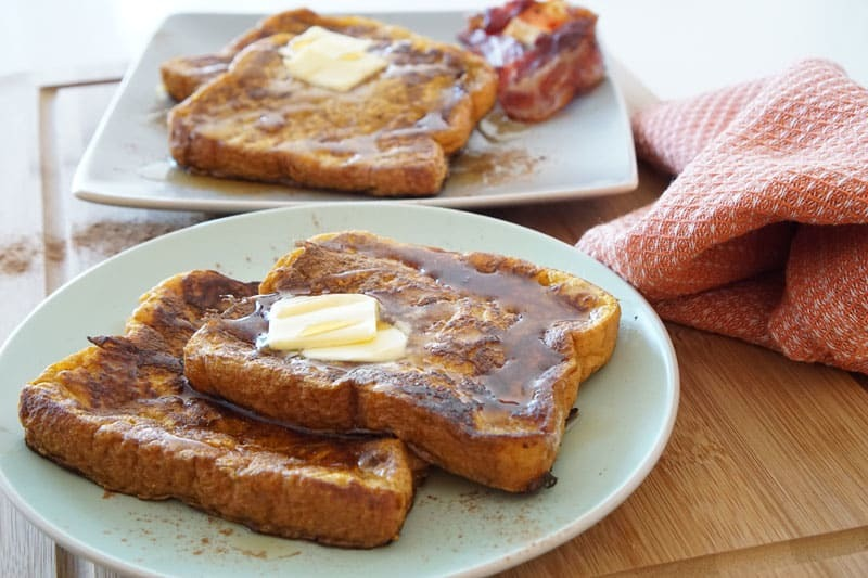 Pumpkin French toast with slabs of butter on white plates.