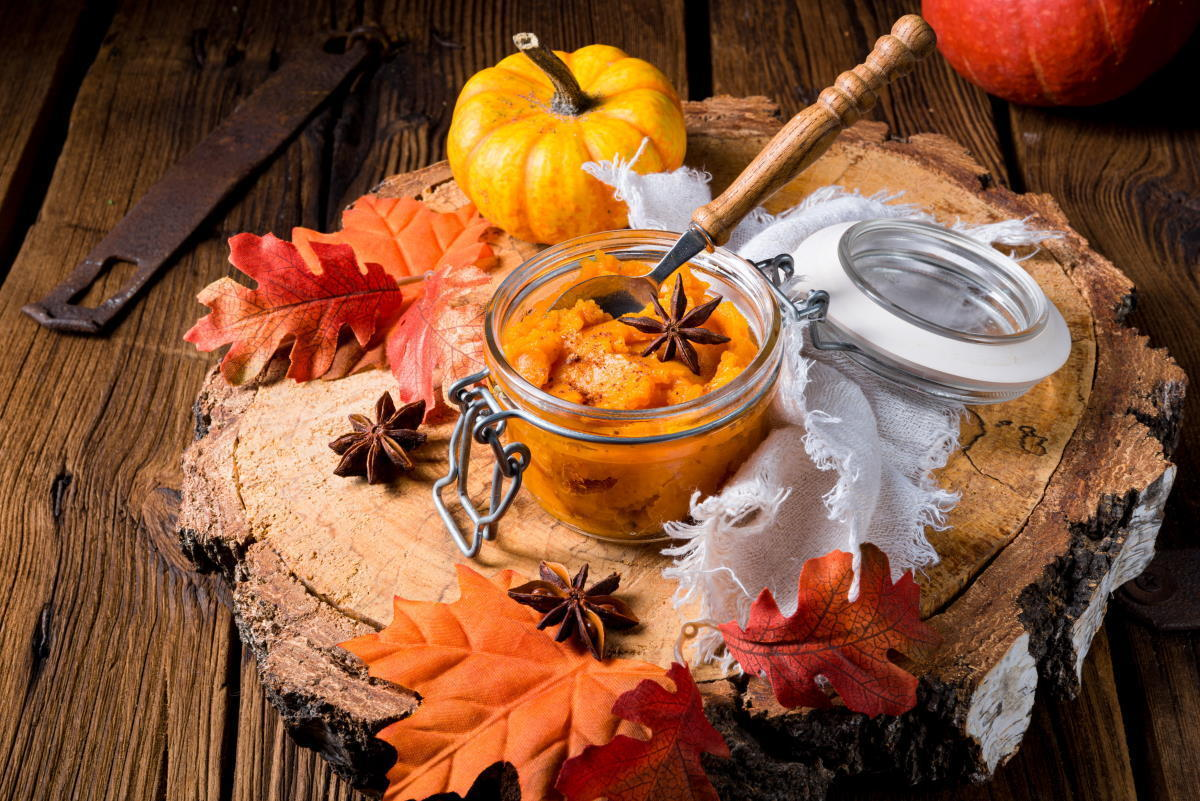 Pumpkin pie filling in a small jar on wooden background, fall leaves and gourds on the side.