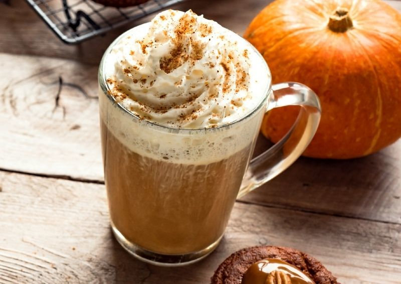Pumpkin spice latte with a pumpkin in the background.